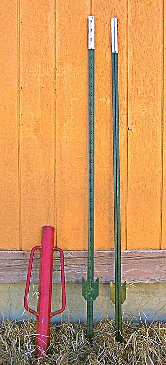 Post pounder - A red-colored post pounder next to two green steel t-posts