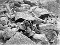 Two men, one probably Charles Ainsworth, navigating along rock wall on Chilkoot Pass, ca 1898 (CURTIS 1805).jpeg