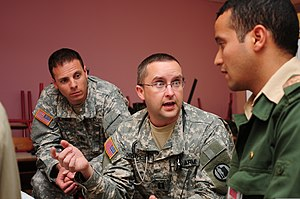 Limited English proficiency - A physician assistant with the Utah State Medical Command, Utah Army National Guard, speaks to an interpreter while working at a humanitarian civic assistance.
