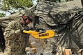 U.S. Navy Utilitiesman 1st Class Anthony W. Miller, assigned to Naval Mobile Construction Battalion 11, saws wood to be used in a construction project while participating in a field exercise (FEX) at Camp 130515-N-UH337-066.jpg