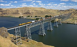 Rail freight transport - A long grain train of the Union Pacific Railroad crossing a bridge in Washington state, United States