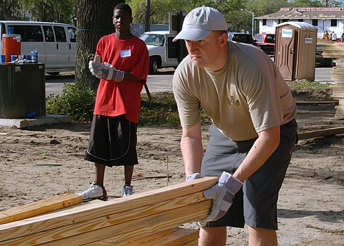 US Navy 060602-N-6159A-001 Chief Aviation Electronics Technician Theodore Person lines up a stack of lumber during a local Habitat for Humanity project at the McNair Park Villas in downtown Jacksonville