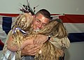 US Navy 061019-N-4238B-040 Boatswain's Mate 2nd Class Trent Bridgman of the Navy Expeditionary Logistics Support Group (NAVELSG) Delta embraces his family upon his return from a six-month deployment in support of the global war.jpg