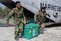 US Navy 071128-N-7955L-016 A Bangladesh Army solider and a Marine Corps aircrew chief unload containers of supplies from the CH-53E Sea Stallion helicopter which is attached to Marine Medium Helicopter Squadron (HMM) 261.jpg