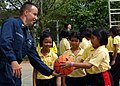 US Navy 080609-N-3581D-028 Aviation Structural Mechanic 2nd Class James Patnoudes, a native of Joliet, Ill., greets Khaobuysri school children with a basketball.jpg
