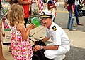 US Navy 080711-N-7869M-084 Lt. Cmdr. Michael Sullivan, assigned to the amphibious transport dock ship USS Nashville (LPD 14), shares a smile with his daughter during the return of the Nassau Expeditionary Strike Group.jpg