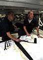 US Navy 081001-N-9116H-013 Aviation structural mechanic Airman John Fulk, left, and aviation structural mechanic Airman Robert Garrison read instructions during a post-test cell procedure on an engine.jpg