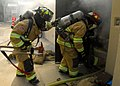 US Navy 090819-N-9573A-007 Firefighters enter a smoke-filled space during a fire saboteur drill.jpg