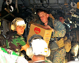 US Navy 090909-N-4010S-069 Marines work with Indonesian military personnel to load a CH-53E Super Stallion helicopter with relief supplies for victims of recent earthquakes and resulting landslides