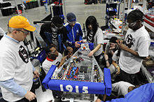 US Navy 100305-N-7676W-182 Cmdr. Jim Grove, from the Office of Naval Research Navy Reserve Program 38, left, helps tudents from McKinley Technology High School make adjustments to their robot.jpg