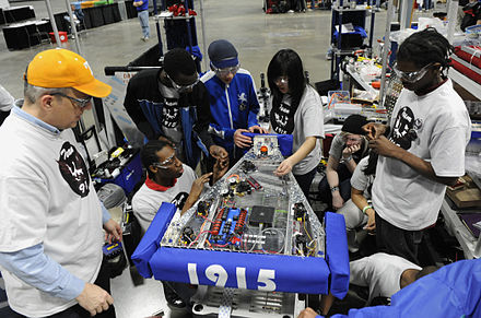 Student participants in the FIRST Robotics Competition, Washington, D.C. US Navy 100305-N-7676W-182 Cmdr. Jim Grove, from the Office of Naval Research Navy Reserve Program 38, left, helps tudents from McKinley Technology High School make adjustments to their robot.jpg