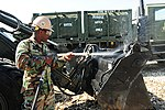 US Navy 100308-N-9643W-083 Equipment Operator 3rd Class Kenneth Moore, from Norfolk, Va., assigned to Naval Mobile Construction Battalion (NMCB) 7, washes down a front-end loader before shipping it from Haiti back to the United.jpg