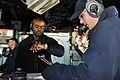 US Navy 111025-N-YX169-387 Operations Specialist Seaman Recruit Patrick Lloyd, right, uses a sound-powered phone to make a report from the bridge o.jpg