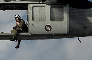 US Navy 111220-N-DR144-761 A Naval Air Crewman assigned to Helicopter Sea Combat Squadron (HSC) 12 guides the pilots of an MH-60S Sea Hawk helicopt.jpg