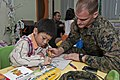 US Navy 111222-N-DX615-107 Sgt. Benjamin Wooden, assigned to the 11th Marine Expeditionary Unit (11th MEU), colors with a boy at Singapore's Child.jpg