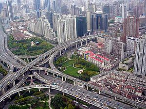 Civil engineering - A multi-level stack interchange, buildings, houses, and park in Shanghai, China.