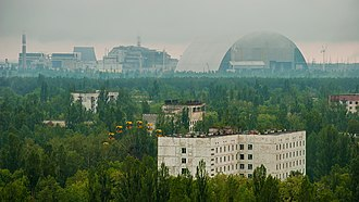 The town of Pripyat abandoned since 1986, with the Chernobyl plant and the Chernobyl New Safe Confinement arch in the distance. Tsentr goroda Pripiat' na fone 4 energoblokaa ChAES.jpg