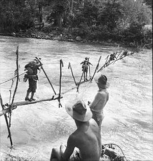 Battle of Buna–Gona - On the road to Buna, Australian troops cross a stream on an improvised bridge. AWM013755