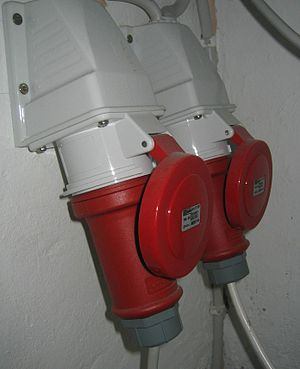 IEC 60309 - Two IEC-60309-style plugs inserted into wall-mounted sockets