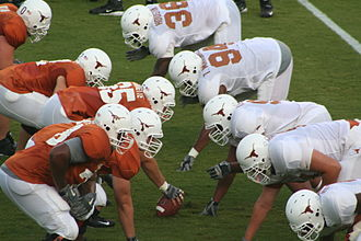 American football positions - The offensive line (on left, in orange jerseys) consists of a center (with ball in hand ready to snap) two guards on either side of him, and two tackles.
