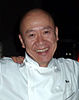 Masa Takayama, a bald-headed smiling middle-aged man wearing a chef's white double-breasted jacket with the name Masa on it