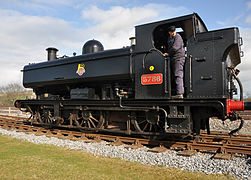 "A pannier tank locomotive is standing on a siding. The locomotive is mainly painted black. On the side of the pannier tank is a crest consisting of a red and white spoked wheel. Across the wheel is a black and white label with the words ""BRITISH RAILWAYS"". A yellow lion stands on the label, above the wheel. On the side of the cab is a red number plate with the edge and number in brass. The rear buffer beam is red."
