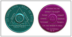Sobriety coin - Alcoholics Anonymous sobriety coins, given for specified lengths of sobriety; on the back is the Serenity Prayer. Here green is for six months of sobriety; purple is for nine months.