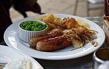 A plate of sausage mash onions and peas Epping Essex, England.jpg