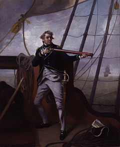 A large man in a blue uniform strikes a dramatic pose holding a telescope on the quarterdeck of a ship. In the distance another ship can be seen with its sails set.
