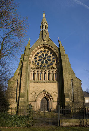 Grade I listed churches in Greater Manchester - The west end of a Gothic Revival church with a small doorway, arcading, a large and elaborate rose window, and a narrow bellcote