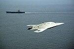 An X-47B Unmanned Combat Air System demonstrator flies near the aircraft carrier USS George H.W. Bush.jpg