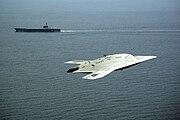 An X-47B Unmanned Combat Air System demonstrator flies near the aircraft carrier USS George H.W. Bush