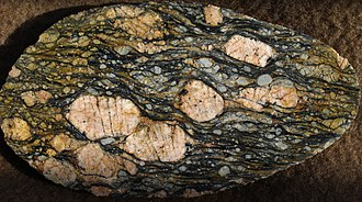 Porphyroclast - Augen mylonite from near Røragen, Norway. This deformed megacrystic granite has large alkali felspar and small plagioclase feldspar porphyroclasts. Sample 18 cm x 10 cm. Many of the larger porphyroclasts have a clear σ-type geometry, consistent with top to the right shear sense.