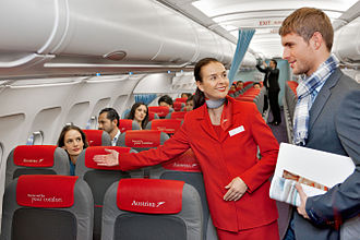 Flight attendant - An Austrian Airlines flight attendant directing a passenger to his seat