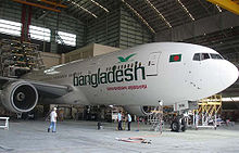 A white aircraft with Bangladesh written along the front side facing right is in a hangar being serviced