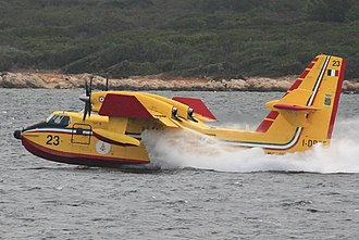 Canadair CL-415 - Italian Vigili del Fuoco refilling near Alghero, spilling excess water through underwing overflow ports