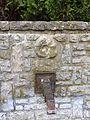Brunnen an der Weggabelung Bischf-Weiß-Straße und Sperrberg, Quellhahn darüber eingemauerter Ammonit.JPG