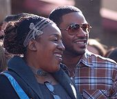 Head and shoulders photo of African-American actors C.C.H. Pounder and Laz Alonso standing together in street clothes