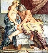 Наполовину одетая мужская фигура с густой бородой и седыми волосами полулежит на кровати, притягивая к себе полуодетую фигуру статной женщины.  Они горячо смотрят друг на друга.