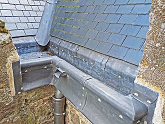Rain gutter - Lead guttering: slate and pitched valley gutter flow into parapet gutter, with downpipe and overflow
