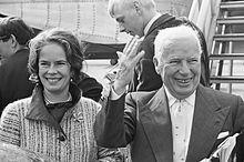 Photographie de Chaplin âgé et de son épouse au pied d'un avion