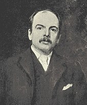 A man with a moustache and a dark suit