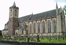 Side view of the nave of a cathedral from outside. Tall arched glass windows run along half the length of the nave from the right. Adjacent to the nave, and to the left of the scene is a cuboid-shaped tower with a conical spire. The foreground is scattered with headstones of a graveyard on green grass.