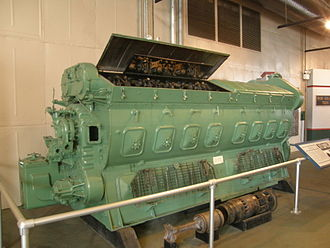 """EMD 567 - An EMD 16-567B on display at the North Carolina Transportation Museum. Shown in the foreground is an """"exploded"""" Power Assembly, with the piston, piston carrier and piston rod (fork type) on the left, and the cylinder liner and cylinder head on the right."""