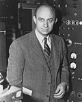 A man looking to the camera, wearing a suit. He is standing in front of a machine.
