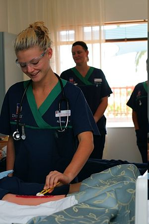 English: Enrolled nursing student dressing a c...