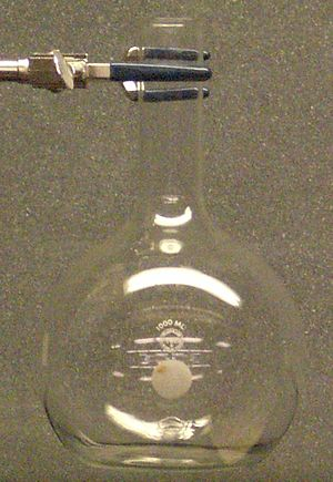 Florence flask - Photograph of a 1 liter Florence flask suspended by its neck with a three-finger clamp