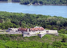 The star-shaped fort is visible in the center of the photograph, with its inner buildings roofed in red. The fort is surrounded by forest, and a body of water (a portion of Lake Champlain) is visible behind the fort.