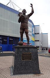 A statue of a footballer lifting a trophy