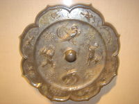 A Tang Dynasty bronze foliate mirror, with decorations of mythical animals and phoenixes, 8th century.